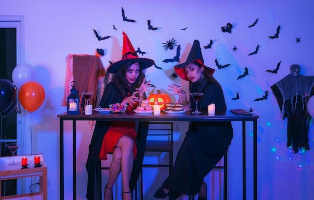 Zwei glückliche junge frauen in schwarzen hexen-halloween-kostümen auf party mit kürbis und cocktails