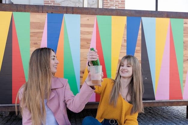 Zwei glückliche junge frauen stoßen mit einem bunten getränk an