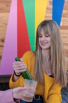 Zwei glückliche junge frauen stoßen mit mehrfarbigem getränk an