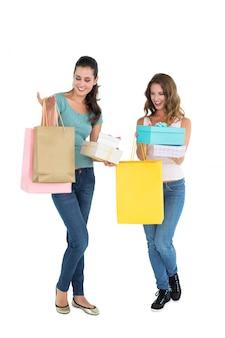 Zwei glückliche junge freundinnen mit einkaufstaschen