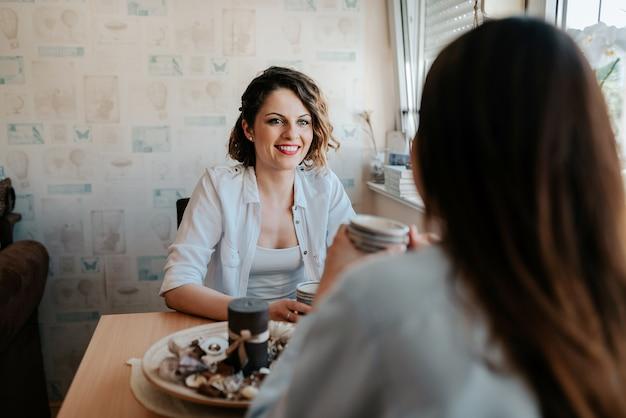 Zwei glückliche junge freundinnen mit kaffeetassen zu hause unterhalten im wohnzimmer.