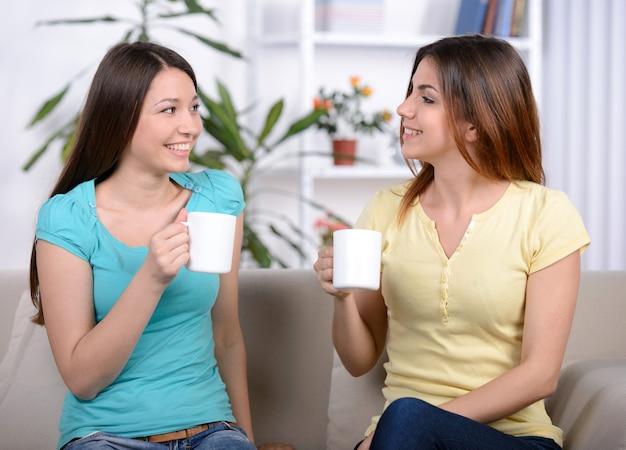 Zwei glückliche junge freundinnen mit kaffeetassen.