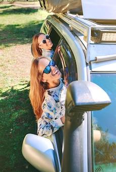 Zwei glückliche junge freundinnen mit sonnenbrille lachen und amüsieren sich durch das fensterauto bei einem roadtrip-abenteuer. weibliche freundschaft und freizeitkonzept.