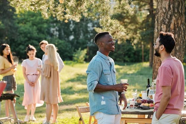 Zwei glückliche junge interkulturelle männer in freizeitkleidung diskutieren das neueste fußballspiel, während sie nach dem abendessen im freien am servierten tisch stehen