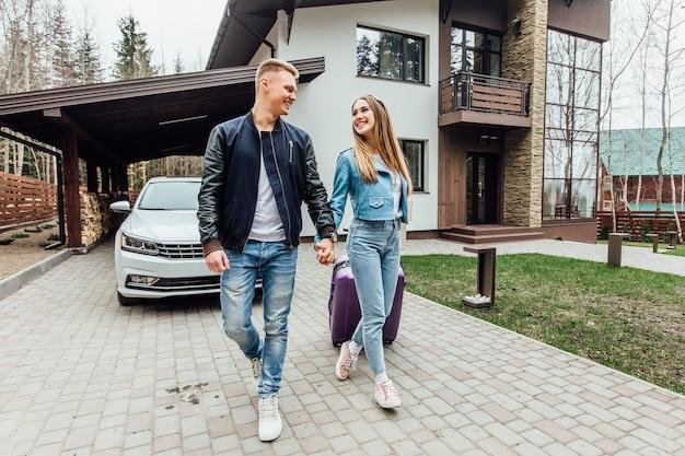 Zwei glückliche, junge leute, die mit violettem koffer und auspackkisten in ein neues haus ziehen. gehen in der nähe von schönen haus.
