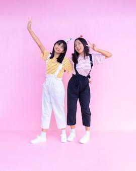 Zwei glückliche junge mädchen, die auf rosa hintergrund stehen.