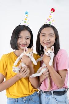 Zwei glückliche junge mädchen tragen partyhut mit zwei katzen auf weißem hintergrund.