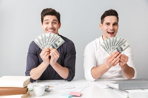 Zwei glückliche junge männer, die geldbanknoten zeigen