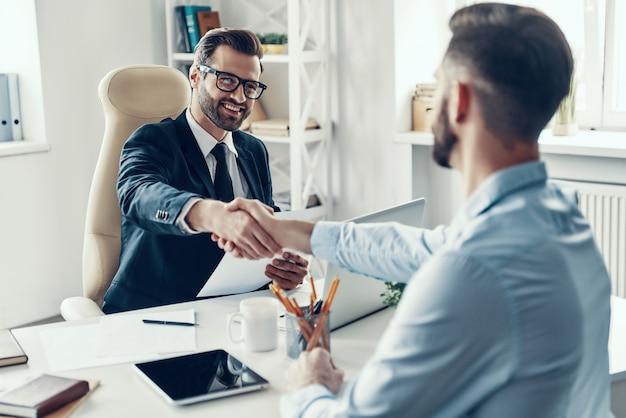 Zwei glückliche junge männer in formeller kleidung, die hände schütteln und lächeln, während sie im büro sitzen