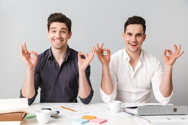 Zwei glückliche junge männer sitzen am schreibtisch und zeigen ok