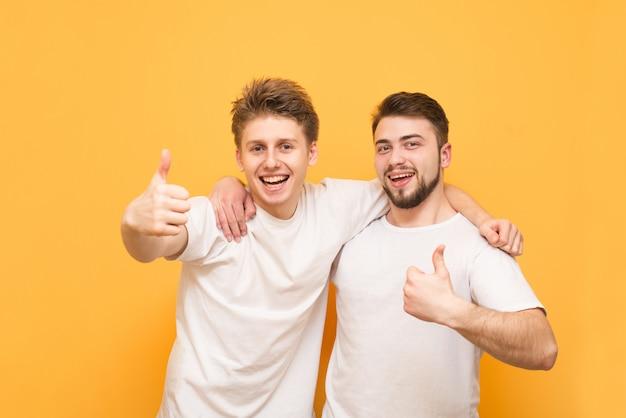 Zwei glückliche junge männer zeigen daumen hoch über gelb. zwei glückliche freunde in weißen t-shirts, die von männern umarmt werden