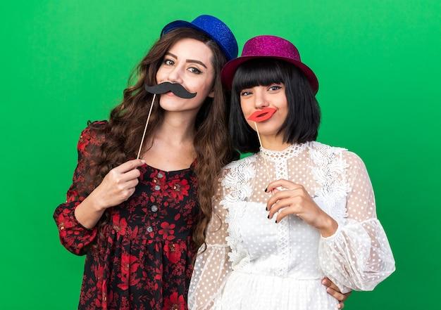 Zwei glückliche junge partymädchen mit partyhut, die beide einen falschen schnurrbart und lippen auf einem stock vor den lippen halten, eine hand auf die taille eines anderen mädchens legen, isoliert auf grüner wand