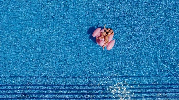 Zwei glückliche junge schöne mädchen mit schönen figuren schwimmen im pool für flamingos Premium Fotos