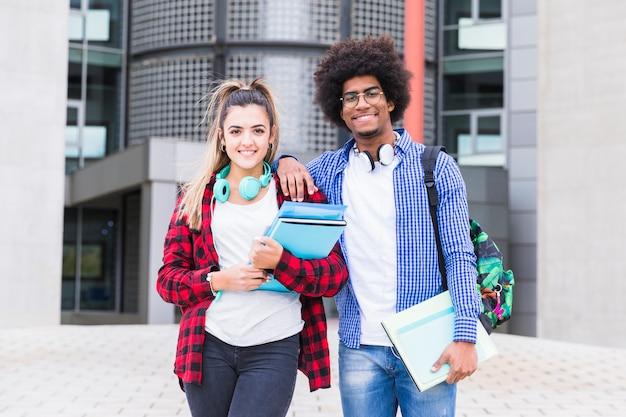 Zwei glückliche junge studenten, die zur kamera stehen vor universitätsgebäude schauen