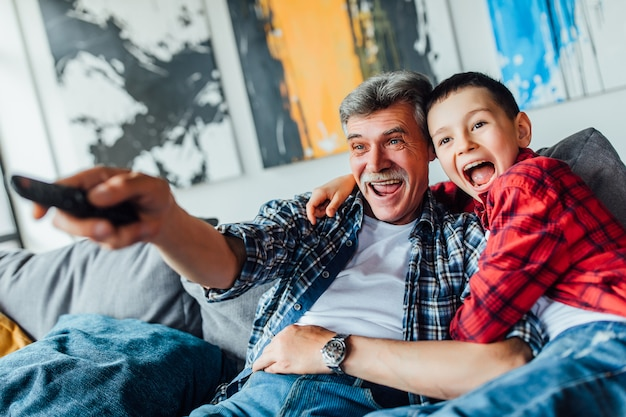 Zwei glückliche jungen, die film zu hause schauen. großvater liebt seinen sohn