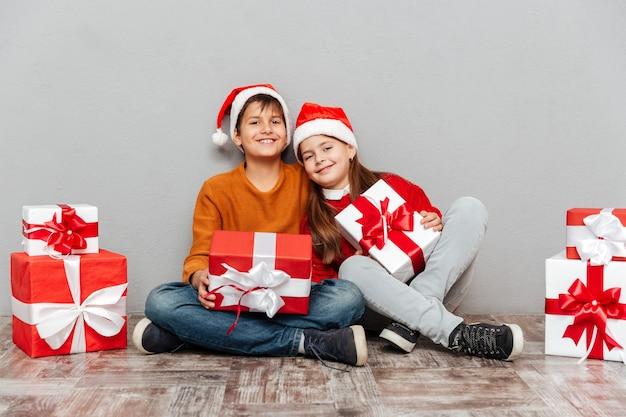 Zwei glückliche jungen und mädchen in weihnachtsmann-hüten mit geschenkboxen