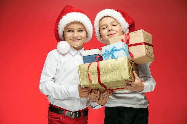 Zwei glückliche jungs in weihnachtsmannmützen mit geschenkboxen auf rot