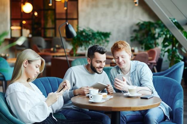 Zwei glückliche kerle mit geräten, die neugierige sachen beobachten, während sie in sesseln im café sitzen und hübsches mädchen, das im smartphone rollt