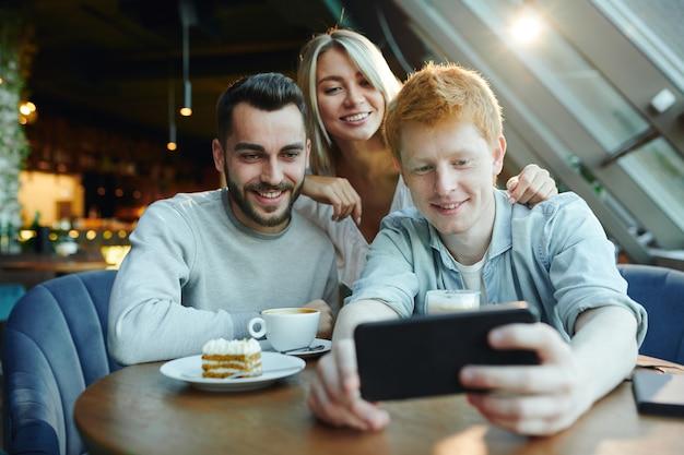 Zwei glückliche kerle und hübsches blondes mädchen machen selfie auf smartphone, während sie am tisch im café für ruhe und chat versammelt werden