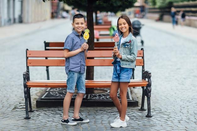 Zwei glückliche kinder an einem sommertag mit süßigkeiten an den händen und lächelnd.