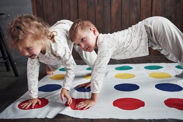 Zwei glückliche kinder, die am twister im haus spielen. bruder und schwester haben eine lustige zeit im urlaub