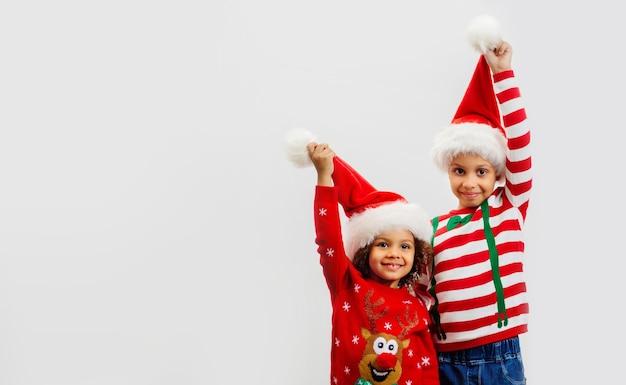 Zwei glückliche kinder in weihnachtskostümen halten rote weihnachtsmützen im gruß auf weißem hintergrund hoch