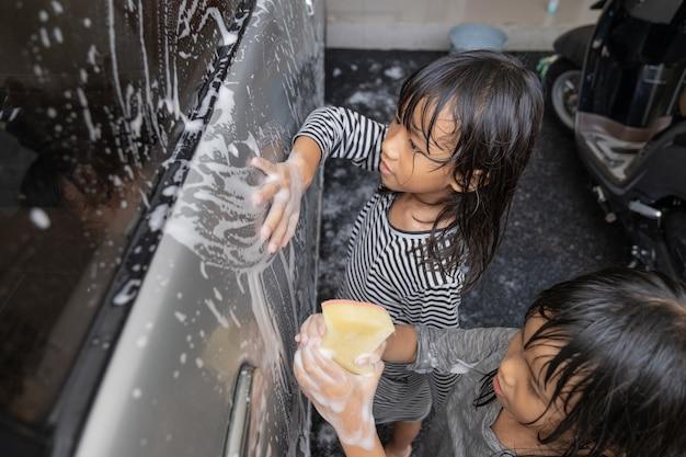 Zwei glückliche kinder waschen papas auto zu hause