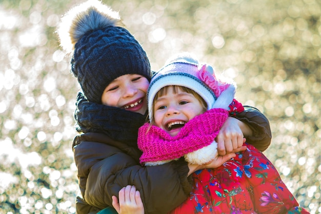Zwei glückliche kinderjungen und -mädchen, die draußen im sonnigen wintertag spielen