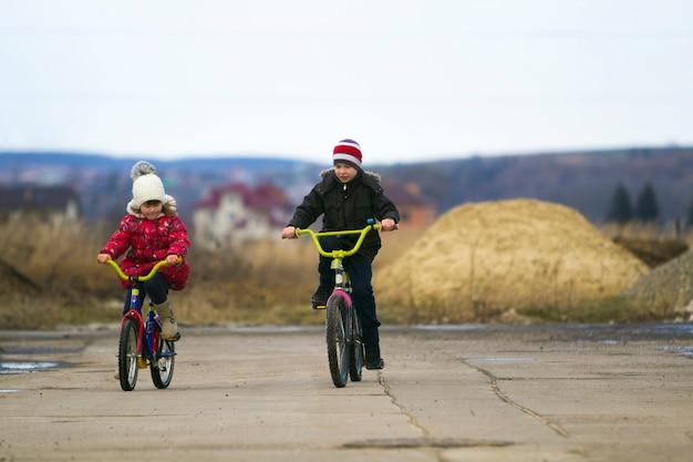 Zwei glückliche kinderjungen und -mädchen, die im freien bei kaltem wetter fahrrad fahren