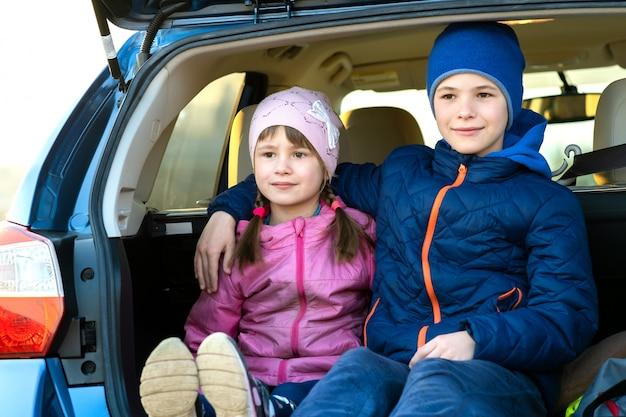 Zwei glückliche kinderjungen und -mädchen sitzen zusammen in einem autokofferraum. fröhlicher bruder und schwester umarmen sich im gepäckraum des familienfahrzeugs. wochenendreise- und urlaubskonzept.