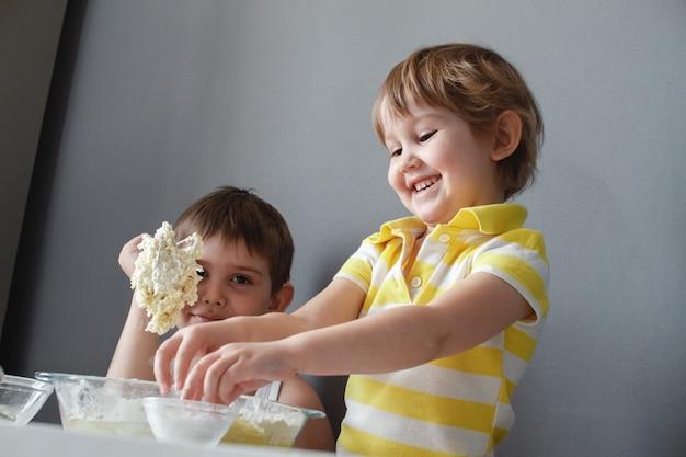 Zwei glückliche kleine kinder, die shortbread machen. sie haben spaß zu lachen und rührten den teig.