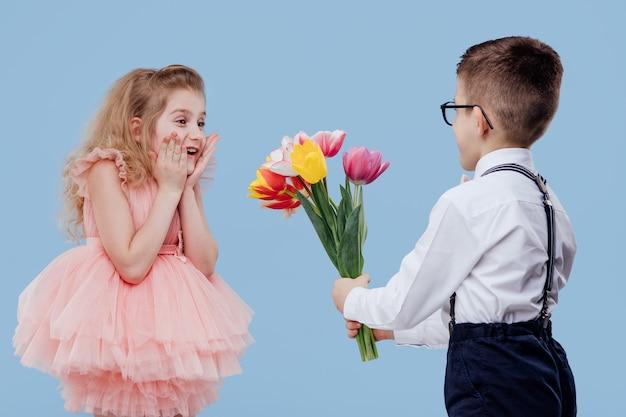 Zwei glückliche kleine kinder. kleiner junge streckt blumen zu einem kleinen mädchen, isoliert auf blauer wand
