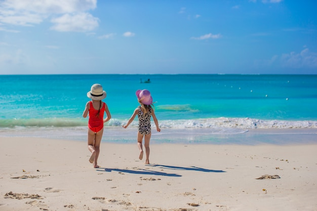 Zwei glückliche kleine mädchen genießen ferien auf weißem strand
