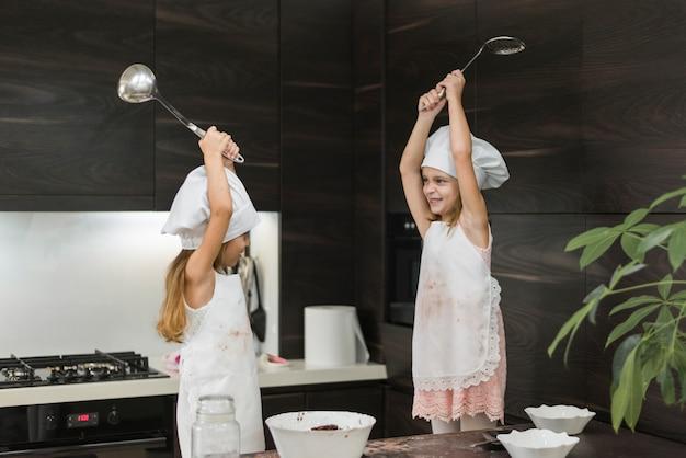 Zwei glückliche kleine mädchen in den hüten des chefs kämpfend mit küchengerät