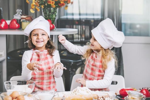 Zwei glückliche kleine mädchen kind kochen mit mehl und teig am tisch in der küche ist schön und schön