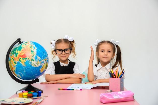 Zwei glückliche kleine mädchen lernen und schreiben in der klasse isolieren