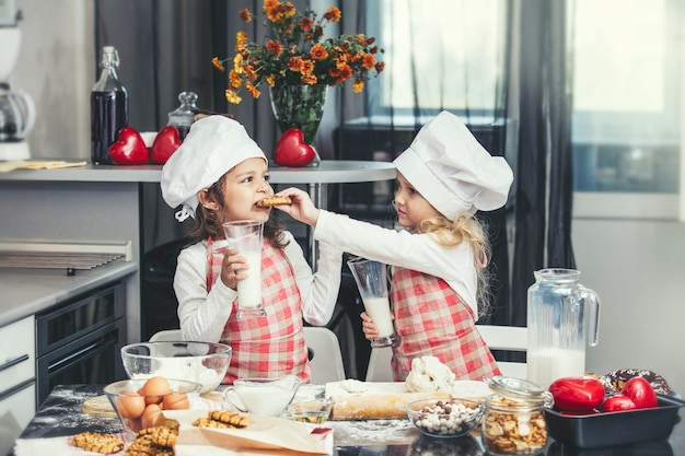 Zwei glückliche kleine mädchen trinken milch und kochen am tisch in der küche ist schön und schön