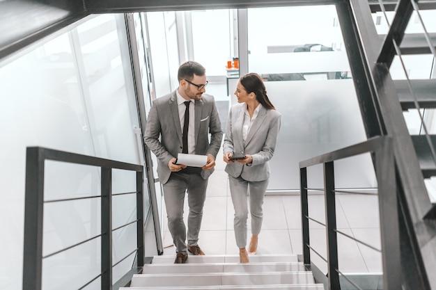 Zwei glückliche kollegen in abendgarderobe steigen die treppe hinauf und unterhalten sich. teamwork ist die fähigkeit, als gruppe auf eine gemeinsame vision hinzuarbeiten.