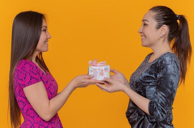 Zwei glückliche lächelnde asiatische frauen, die internationalen frauentag feiern