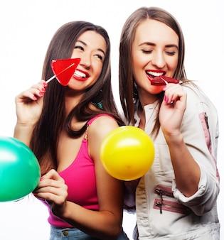 Zwei glückliche mädchen, die farbige luftballons und süßigkeiten lächeln und halten