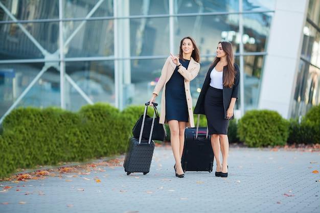 Zwei glückliche mädchen, die zusammen ins ausland reisen und koffergepäck im flughafen tragen