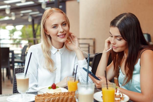 Zwei glückliche mädchen, die zusammen musik mit geteilten kopfhörern im netten café hören