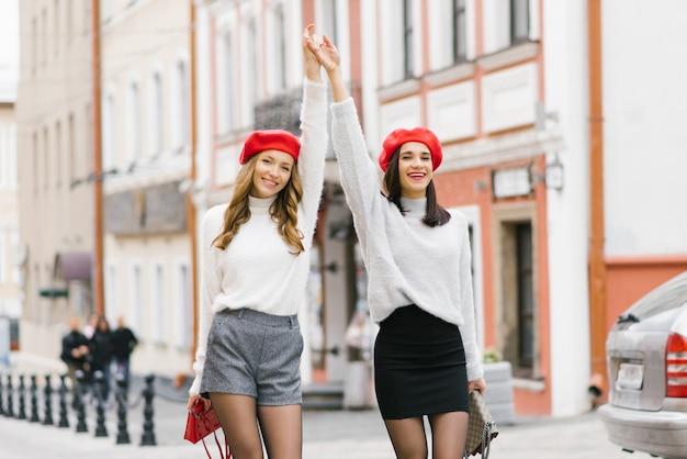 Zwei glückliche mädchen freundinnen halten die hände und hob sie auf, sie lächeln. brünette und braunhaarige frau in roten baskenmützen auf den straßen