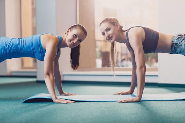 Zwei glückliche mädchen führen sportübung am training durch