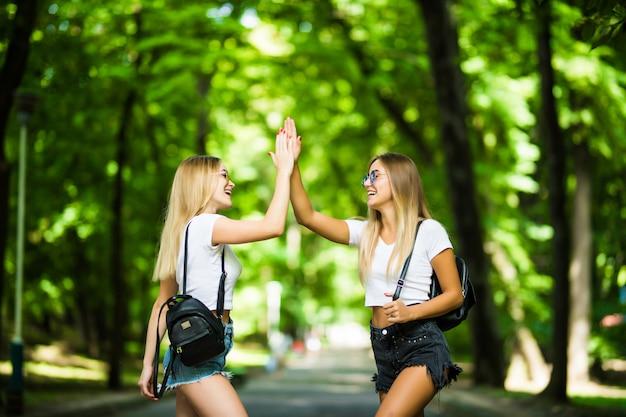 Zwei glückliche mädchen geben hoch und feiern erfolg für genehmigte prüfungen in einem park