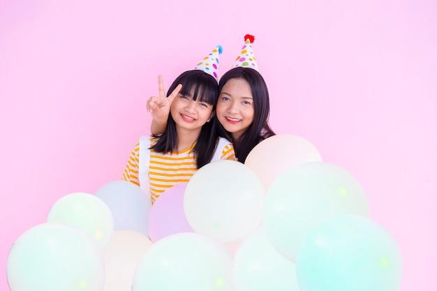 Zwei glückliche mädchen halten ballon auf rosa hintergrund.