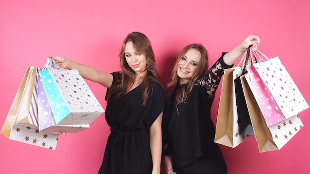 Zwei glückliche mädchen halten pakete in ihren händen und betrachten die kamera über einem rosa hintergrund