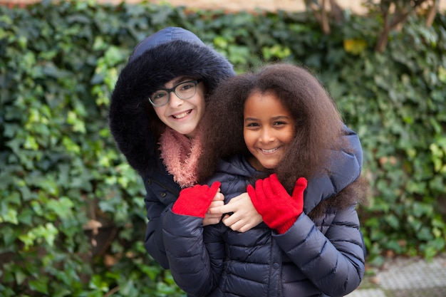 Zwei glückliche mädchen im winter mit mänteln