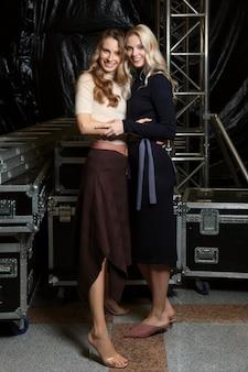 Zwei glückliche mädchen in gestrickten kleidern hinter den kulissen der modewoche