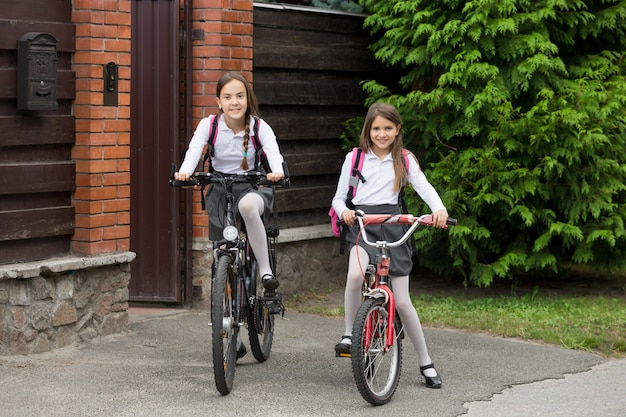 Zwei glückliche mädchen in schuluniform, die auf fahrrädern zur schule fahren